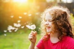 Dente-de-leão de sopro e riso da menina encaracolado pequena fotografia de stock