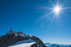 Dente Del Gigante in the blue sky with Sun. The Dente Del Gigante shooted from the clabeway station of Punta Helbronner in a sunny day with blue sky and Sun rays stock images