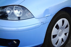 Dented Car Front Wing. Closeup of a light blue dented front wing of small car Royalty Free Stock Photo