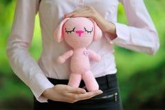 Dentelez l'amigurumi tricoté de lièvres dans les mains d'une fille Images stock
