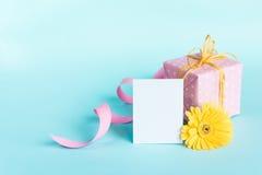 Dentelez le boîte-cadeau pointillé, la fleur jaune de gerbera et la carte vide au-dessus d'un fond bleu Image stock