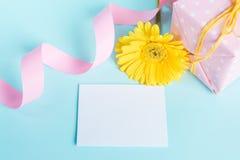 Dentelez le boîte-cadeau pointillé, la fleur jaune de gerbera et la carte vide au-dessus d'un fond bleu Photographie stock libre de droits