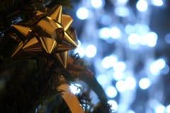 Dentelle de cadeau d'or sur l'arbre de Noël avec des lumières de Noël Images stock
