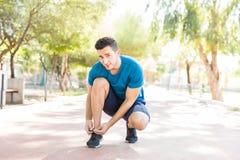 Dentelle de Tying His Shoe d'athlète avant le fonctionnement en parc photo libre de droits