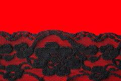 Dentelle florale noire sur le rouge Image stock