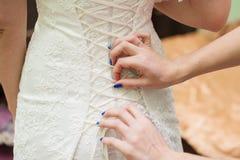 Dentelles de robe de demoiselles d'honneur au dos d'une jeune mariée Photos stock