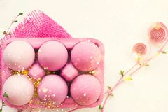 Dentelli le uova di Pasqua colorate in scatola rosa, con la decorazione rosa, su w Fotografia Stock