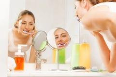 Dentes atrativos da limpeza da mulher na manhã fotos de stock