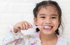 Dentes bonitos asiáticos pequenos da escova da menina imagens de stock royalty free