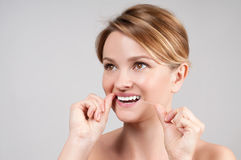 Dentes bonitos da limpeza da mulher com fio dental fotografia de stock