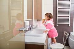Dentes da limpeza da criança no banheiro imagens de stock royalty free