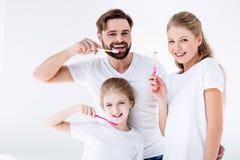 Dentes da limpeza da família com escovas de dentes junto no branco foto de stock royalty free