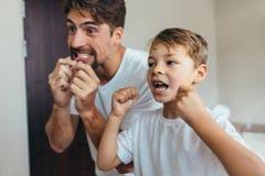 Dentes da limpeza do pai e do filho com fio dental imagens de stock royalty free