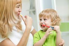 Dentes de escovadela bonitos da mãe e da criança no banheiro imagens de stock
