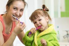 Dentes de escovadela da filha da mamã e da criança no banheiro imagem de stock