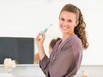 Dentes de escovadela da jovem mulher feliz no banheiro fotografia de stock