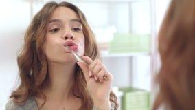 Dentes de escovadela da jovem mulher no banheiro do espelho em casa Limpe os dentes, floss, cuidados dent?rios video estoque