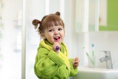 Dentes de escovadela da menina da criança no banheiro fotos de stock royalty free