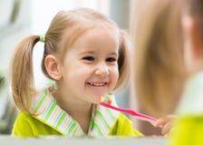 Dentes de escovadela da menina da criança no banheiro imagens de stock royalty free
