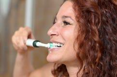 Dentes de escovadela da mulher bonita ao sorrir fotografia de stock royalty free