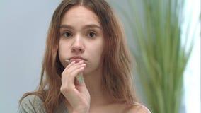Dentes de escovadela da mulher bonita com a câmera da parte dianteira da escova de dentes e do dentífrico vídeos de arquivo