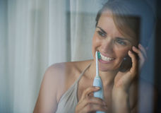 Dentes de escovadela da mulher e móbil falador imagem de stock royalty free