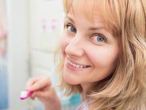 Dentes de escovadela da mulher no banheiro foto de stock royalty free