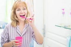 Dentes de escovadela da mulher no banheiro fotografia de stock royalty free