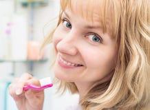 Dentes de escovadela da mulher no banheiro foto de stock