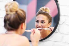 Dentes de escovadela da mulher nova no banheiro fotografia de stock royalty free