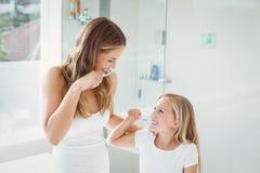 Dentes de escovadela de sorriso da mãe e da filha foto de stock royalty free