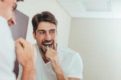 Dentes de escovadela do homem no banheiro imagem de stock
