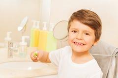 Dentes de escovadela do menino feliz da criança no banheiro foto de stock