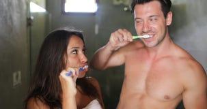 Dentes de escovadela dos pares no banheiro, no homem alegre e na higiene fazendo de sorriso feliz da manhã da mulher filme