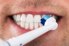 Dentes do homem com escova de dentes elétrica Imagens de Stock Royalty Free