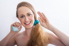 Dentes Flossing da jovem mulher no estúdio branco Imagem de Stock