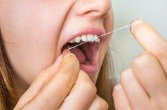 Dentes flossing da mulher com fio dental fotos de stock