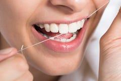 Dentes Flossing da mulher em casa foto de stock royalty free