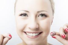 Dentes Flossing e sorriso da mulher caucasiano Cuidados dentários e oral imagem de stock