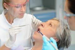 Dentes pacientes idosos da mulher do controle dental da equipe imagens de stock