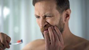 Denti dell'uomo caucasico e sangue di spazzolatura sullo spazzolino da denti, cure odontoiatriche, dolore vedere fotografia stock