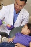 Denti della spazzola di Demonstrating How To del dentista al giovane paziente femminile Fotografia Stock Libera da Diritti