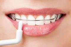 Denti di pulizia con il fermo immagine stock