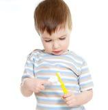 Denti di pulizia del bambino isolati su priorità bassa bianca Fotografia Stock