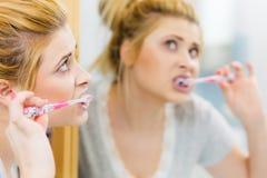 Denti di pulizia di spazzolatura della donna in bagno Immagine Stock Libera da Diritti