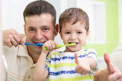 Denti di spazzolatura del figlio del bambino e del papà in bagno Immagine Stock