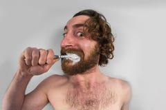 Denti di spazzolatura dell'uomo barbuto Fotografia Stock Libera da Diritti