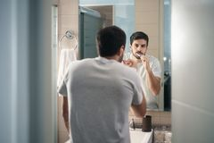Denti di spazzolatura dell'uomo ispano in bagno alla mattina immagine stock