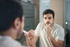 Denti di spazzolatura dell'uomo ispano in bagno alla mattina fotografie stock libere da diritti