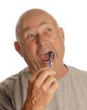 Denti di spazzolatura dell'uomo maggiore Fotografia Stock